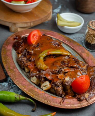 Traditional turkish iskender kebab served with vegetable and sauce Фото со стока