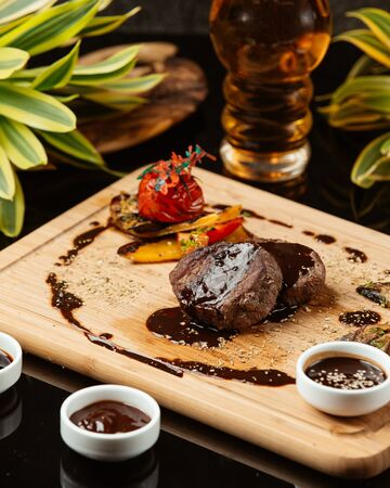 Two pieces of round small steaks with pomegranate sauce and grilled vegetables Stok Fotoğraf - 130621184