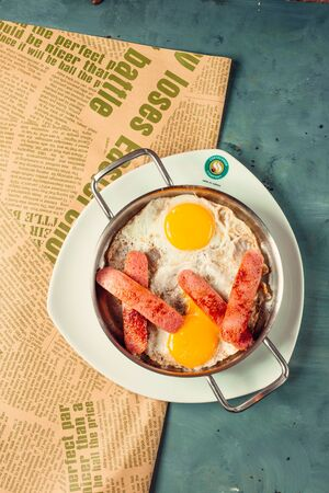Sunny up side eggs for breakfast with half cutted and fried sausages Banco de Imagens