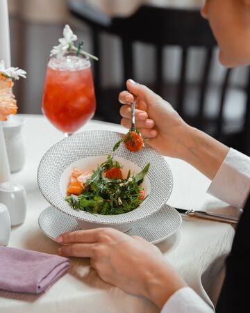 Woman eating vegetable salad with tomato, bell pepper, dill and rocket Stock Photo