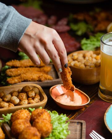 Woman dipping chicken croquette into sauce in beer setup with nuts