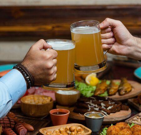 Dos amigos tintineo de jarras de cerveza en la configuración de beew Foto de archivo