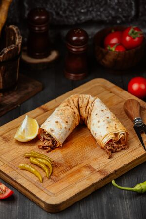 Long chicken wrap with lemon and pickled peppers on wooden board