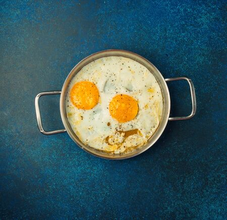 Perfect sunny side up fried eggs in simple blue background Banco de Imagens