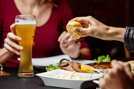 Women squeezing lemon on top of string-cheese beer snack Фото со стока