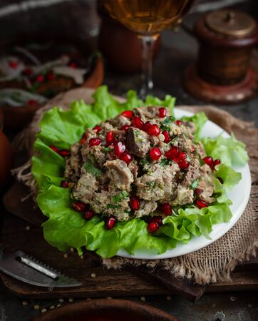 Grated walnut salad with slices of meat and pomegranate