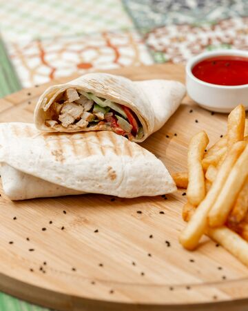 Chicken wrap served with french fries Фото со стока