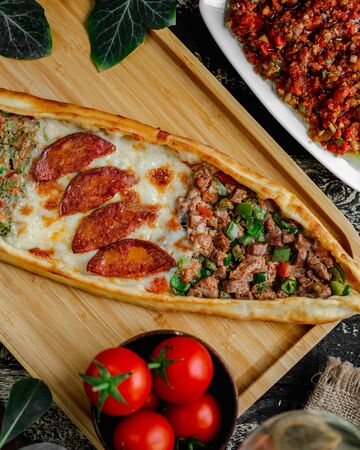 Mixed pide with meat, sausage and vegetables