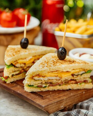 Club sandwich topped with olives