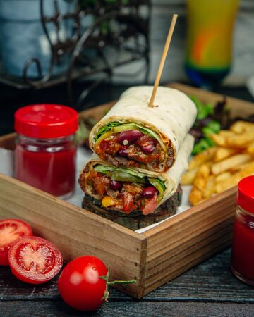Meat wrap with ketchup and fries Фото со стока