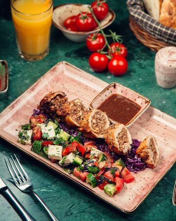 Sliced meat rolls with vegetable salad