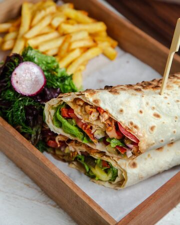 Chicken wrap with vegetables and french fries