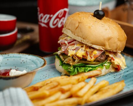 Cheeseburger topped with olives and fries Stockfoto