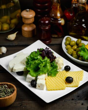Mix of cheese served with basil and olives Фото со стока