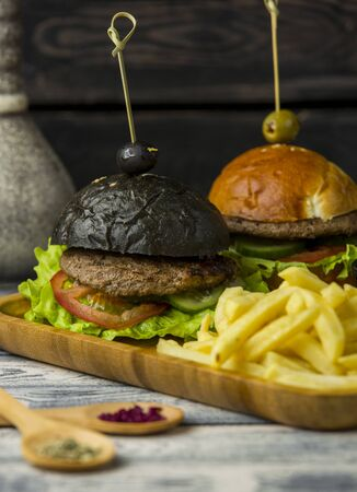black burger and white burger with french fries in wood platter