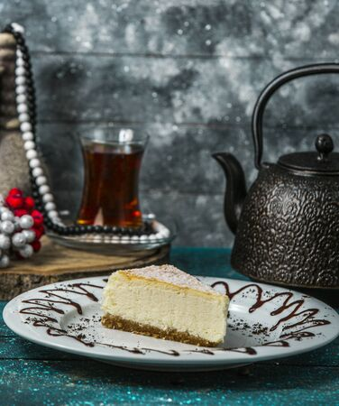 cheesecake slice in white plate served with black tea Banco de Imagens