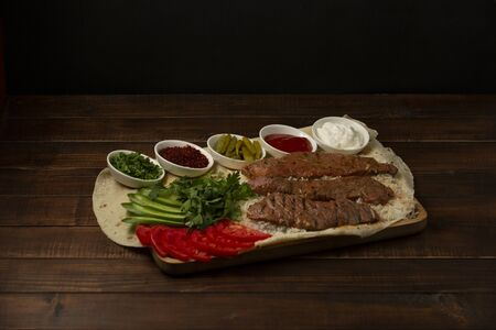 beef fillet kebab slices on rice, served with tomato, cucumber, herbs, sauces
