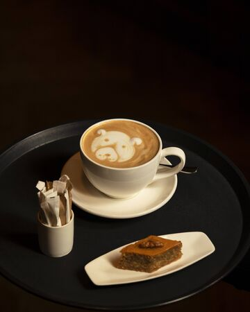 cup of cappuccino with dog latte art served with pakhlava in dark background