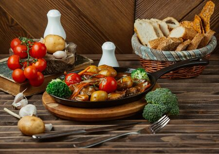 roasted beef in sauce with potatoes, tomatoes, broccoli, carrots in cast iron pan Stock fotó