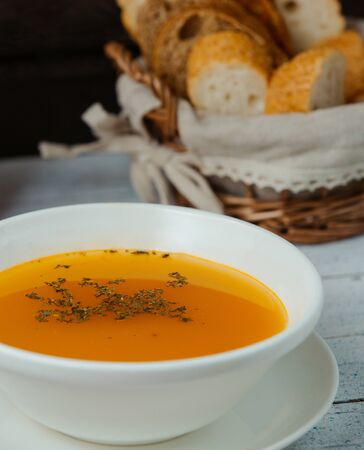 close up of lentil soup garnished with dried mint, served with bread