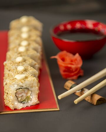 sushi rolls covered with sesame with shrimp and avocado
