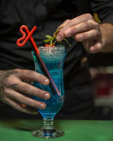 man garnishes glass of blue lagoon with mint leaves