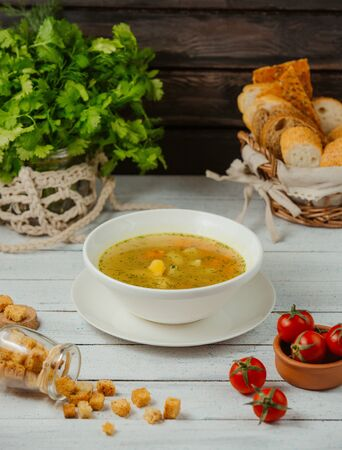 a bowl of chicken soup with potato, carrot and dill served with bread slices
