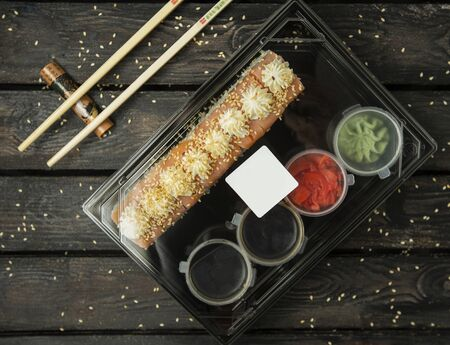 plastic box of shushi rolls for delivery with salmon, sauces, wasabi, ginger