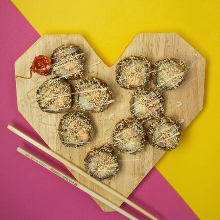 top view of fried sushi rolls in heart-shaped with ginger and wasabi