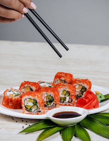 woman holding chopsticks to take sushi rolls with red tobiko