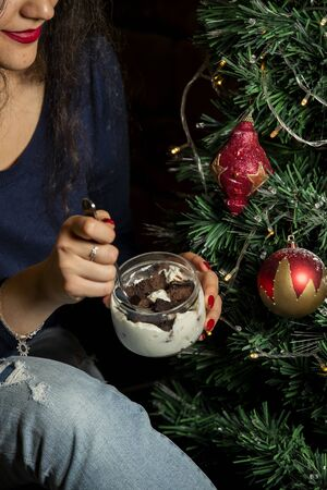 woman eating chocolate cake cubes in whipped cream from glass jar Standard-Bild