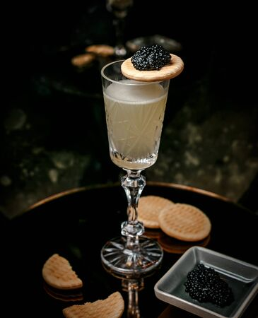 white wine in crystal glass served with black caviar and cookies