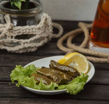 grape leaves dolma stuffed meat and rice, garnished with lemon slices