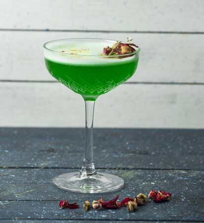 green cocktail in crystal glass garnished with dried rose buds Archivio Fotografico
