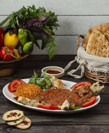 beef kebab garnished with tomato slice, served with bulgur, bread and vegetables