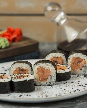 close up of salmon maki rolls garnished with sesame