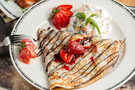 sweet crepe with powder and strawberries