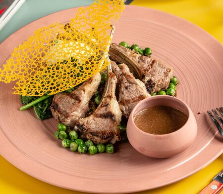 plate of lamb ribs kebab served with green peas, spinach and sauce