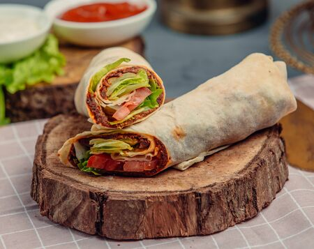meat and vegetables in lavash on wooden board Stockfoto