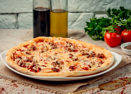 pizza with fried meat on the table