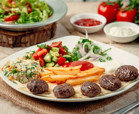 turkish traditional kofte with french fries and vegetables