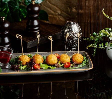 potato balls served with fresh vegetables as side dish