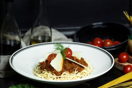 spaghetti bolognese garnished with cherry tomatoes and parmesan slices