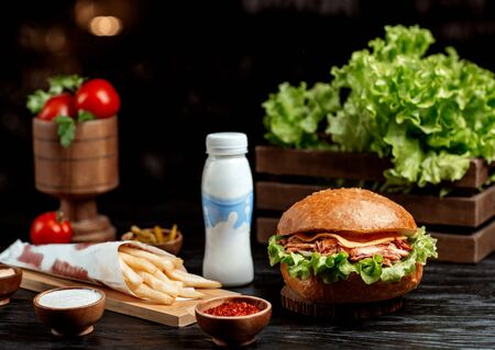 chicken burger with cheese, lettuce, pickled cucumber, fries and sauces