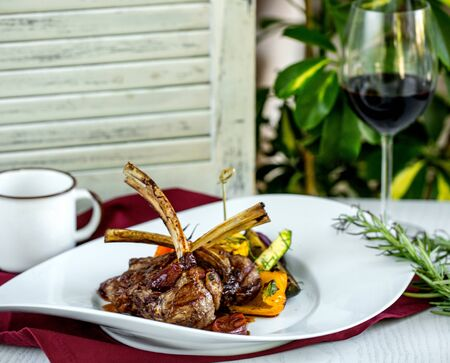 lamb ribs kebab served with grilled vegetables, avocado and hebs