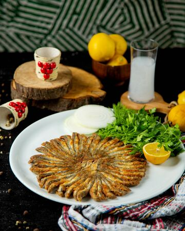 fried sprats in round shape served with parsley and lemon