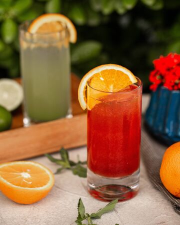 a glass of red juice garnished with orange slice