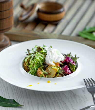 bowl of salad with fried potatoes, arugula, cucumber, lettuce and Stok Fotoğraf