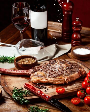 beef steak garnished with kosher salt on wood serving board