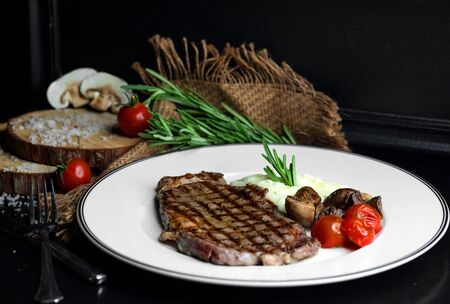 beef steak served with rice, mushroom and tomato